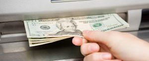Cash Handling Solutions - Hand Getting Cash at ATM machine photo