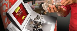 NationalLink Coin Redemption - Person pouring jar of coins in coin counter machine photo