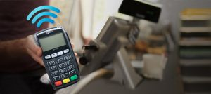 Merchant Services Wireless Payment Solutions - Guy Holding POS Terminal Photo