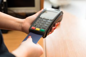 Merchant Services Payment Solutions Point of Sale - person using terminal inserting emv card to pay photo