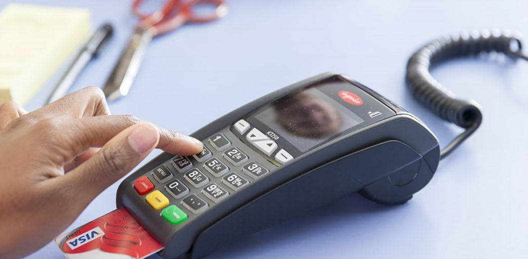 NationalLink Merchant Services Payment Solutions - Person punching numbers on EMV terminal photo